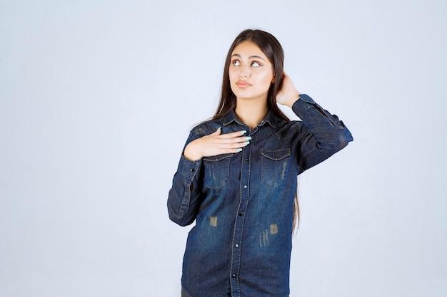 Jeune femme en chemise en jean pointant sur elle-même