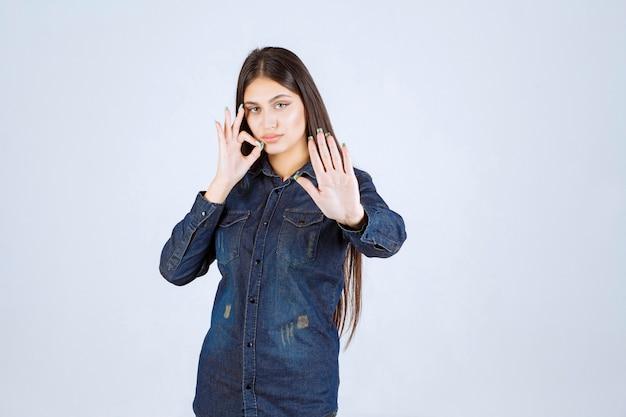 Jeune femme en chemise en jean pointant sur sa bouche et demandant de se taire