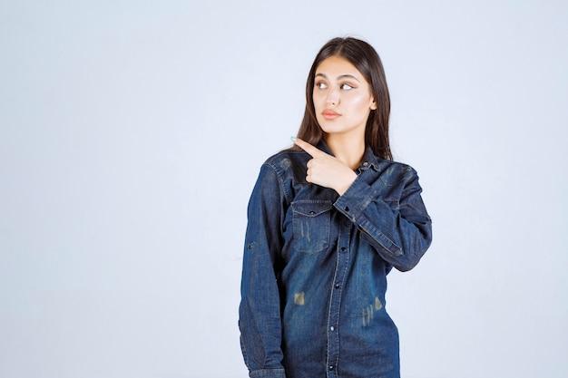 Jeune femme en chemise en jean pointant vers le côté gauche