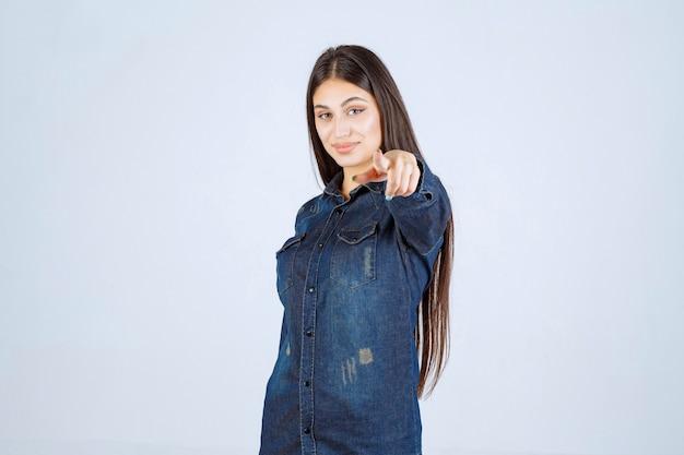 Jeune femme en chemise en jean pointant vers la personne en face d'elle