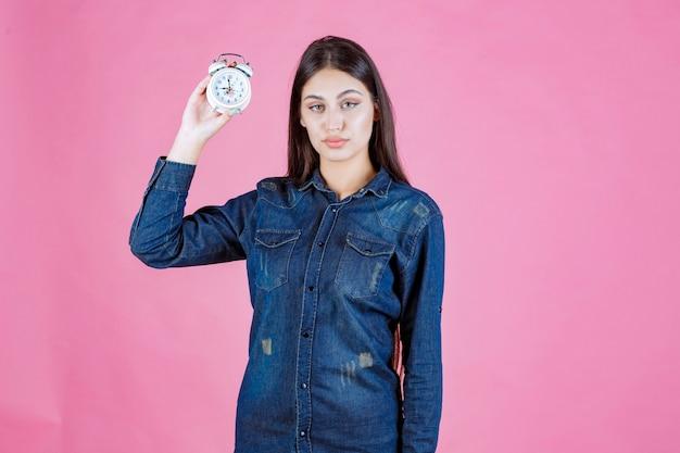 Jeune femme en chemise en jean tenant et faisant la promotion d'un réveil