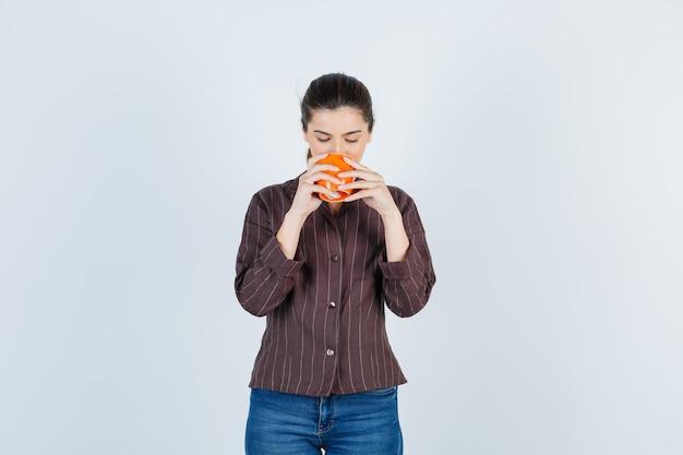 Jeune femme en chemise, jeans buvant dans une tasse et semblant ravie, vue de face.