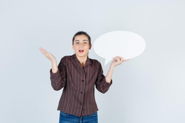 Jeune femme en chemise, jeans étalant la paume, gardant une affiche en papier et l'air curieux, vue de face.