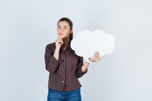 Jeune femme en chemise, jeans avec la main sur le menton, gardant une affiche en papier et l'air réfléchi, vue de face.