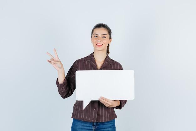 Jeune femme en chemise, jeans montrant le signe v, gardant une affiche en papier et l'air heureux, vue de face.