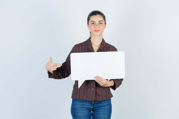 Jeune femme en chemise, jeans pointant sur le côté, gardant une affiche en papier et ayant l'air satisfaite, vue de face.