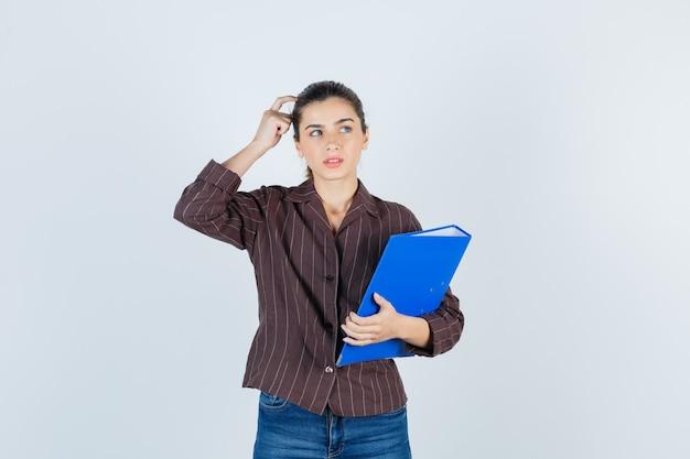Jeune femme en chemise, jeans tenant un dossier, debout dans une pose de réflexion et semblant raisonnable, vue de face.