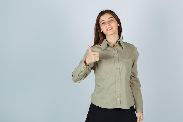 Jeune femme en chemise, jupe montrant le pouce vers le haut et l'air heureux, vue de face.