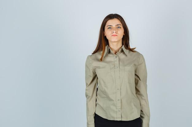 Jeune femme en chemise, jupe pinçant les lèvres et semblant nerveuse, vue de face.