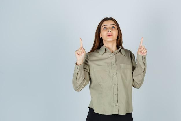 Jeune femme en chemise, jupe pointant vers le haut et à l'espoir, vue de face.