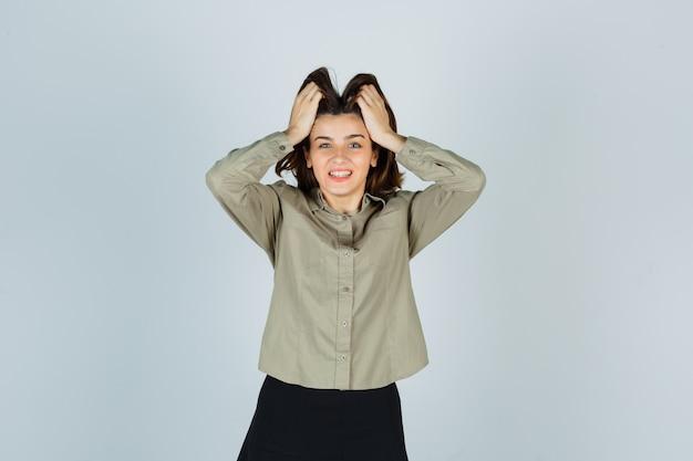 Jeune femme en chemise, jupe serrant la tête avec les mains et l'air heureux