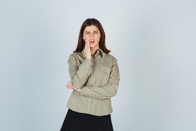 Jeune femme en chemise, jupe souffrant de maux de dents et à la douleur