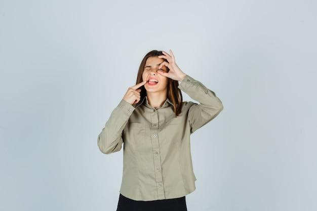 Jeune femme en chemise montrant signe ok sur l'oeil, pointant sur ses dents et à la pensif