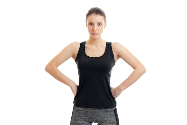 Une jeune femme à la chemise noire a ses mains sur les côtés et se penche sur un appareil photo isolé sur un mur blanc