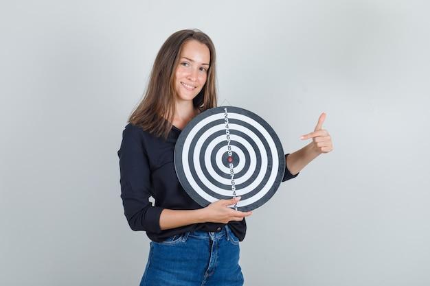 Jeune femme en chemise noire, short en jean, doigt pointé sur le jeu de fléchettes et à l'espoir