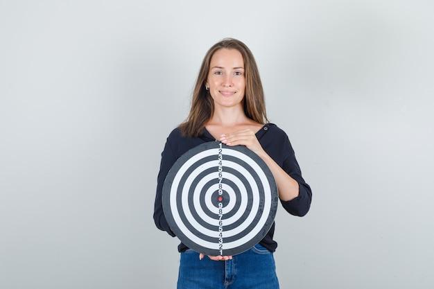Jeune femme en chemise noire, short en jean tenant un jeu de fléchettes et à la joyeuse