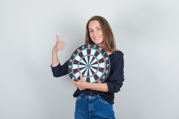 Jeune femme en chemise noire, short en jean tenant le jeu de fléchettes avec le pouce vers le haut et souriant