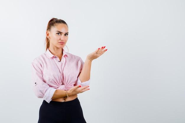 Jeune femme en chemise, pantalon levant la main en signe de questionnement et à la perplexité, vue de face.