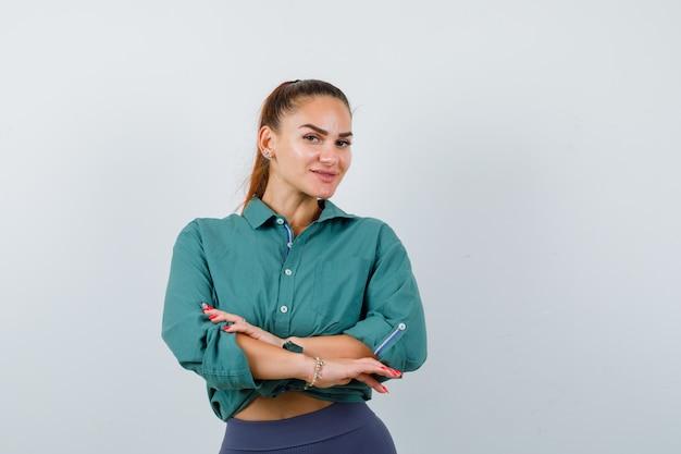 Jeune femme en chemise, pantalon avec les mains devant elle et semblant ravie, vue de face.