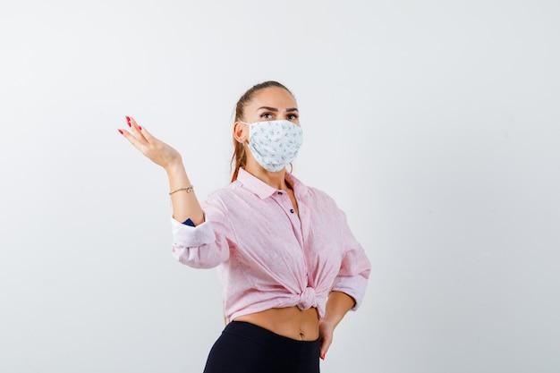 Jeune femme en chemise, pantalon, masque étalant la paume de côté et à la vue de face, confiant.