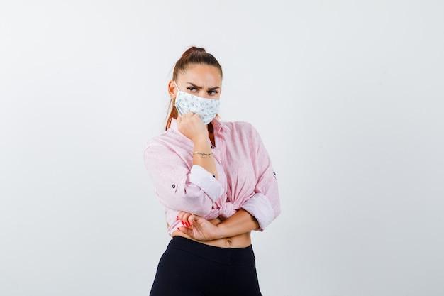 Jeune femme en chemise, pantalon, masque étayant le menton sur le poing et regardant pensif, vue de face.