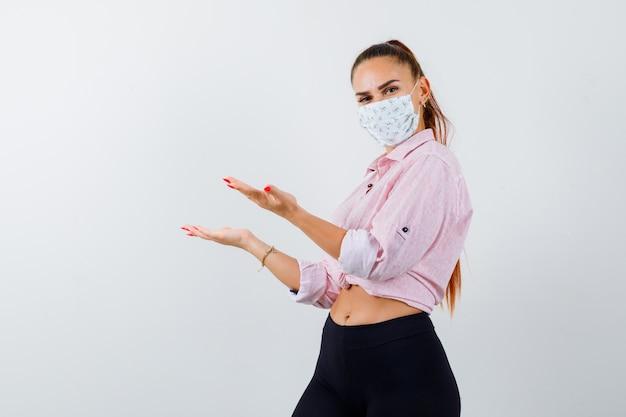 Jeune femme en chemise, pantalon, masque faisant semblant de tenir quelque chose et l'air fier.