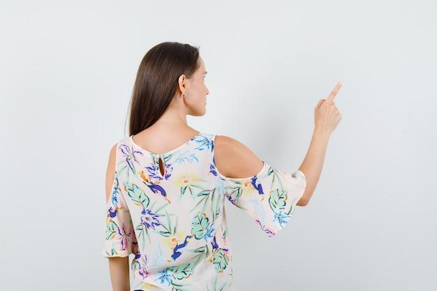 Jeune femme en chemise pointant sur quelque chose et à la vue de dos, focalisée.