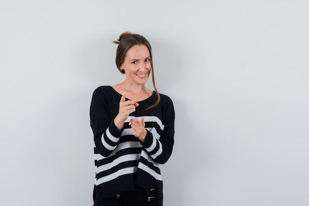 Jeune femme en chemise pointant vers l'avant et à la joyeuse