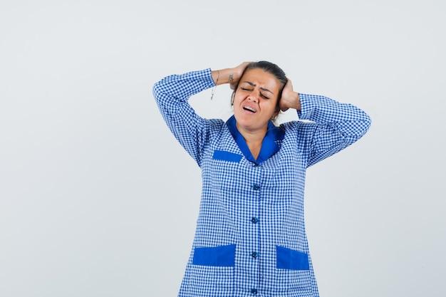 Jeune Femme En Chemise De Pyjama Vichy Bleu Mettant La Main Sur La Tête, Ayant Mal à La Tête Et à L'ennui, Vue De Face. Photo gratuit