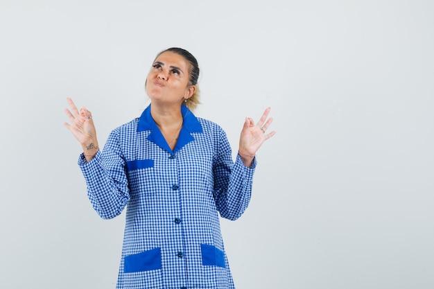 Jeune femme en chemise de pyjama vichy bleu montrant des signes ok avec les deux mains et à la jolie vue de face.