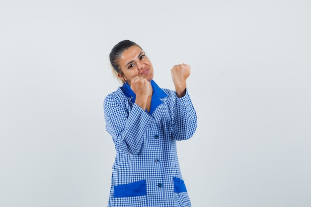 Jeune Femme En Chemise De Pyjama Vichy Bleu Serrant Les Poings Et à La Jolie Vue De Face. Photo gratuit