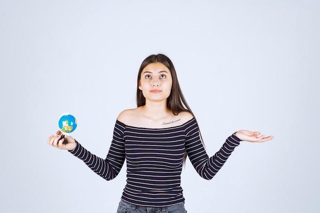 Jeune femme en chemise rayée tenant un mini globe et a l'air excité