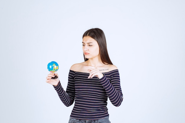Jeune femme en chemise rayée tenant un mini globe et deviner une place dessus