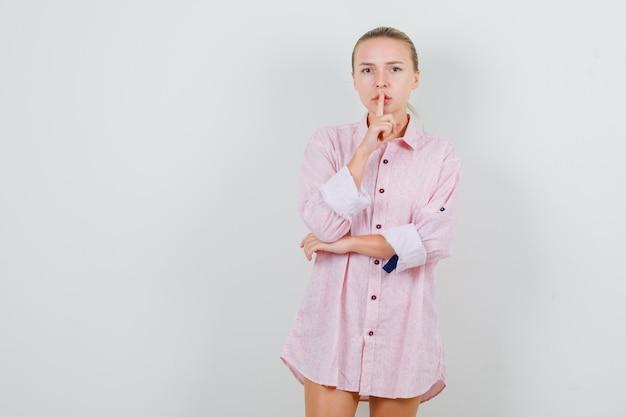 Jeune femme en chemise rose montrant le geste de silence et à la prudence