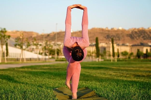 Jeune femme en chemise rose et pantalon sur l'herbe à l'intérieur du parc vert méditant et faisant du yoga dans des poses différentes