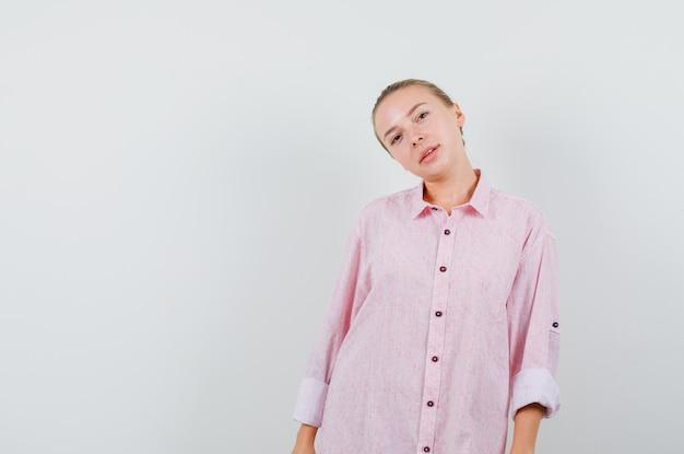 Jeune femme en chemise rose s'inclinant la tête sur l'épaule