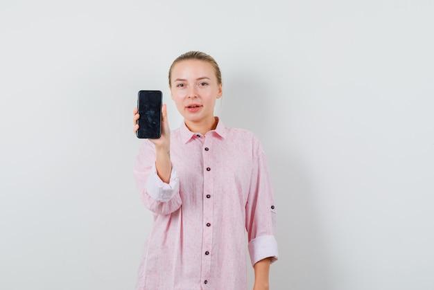 Jeune femme en chemise rose tenant un téléphone mobile et à la satisfaction