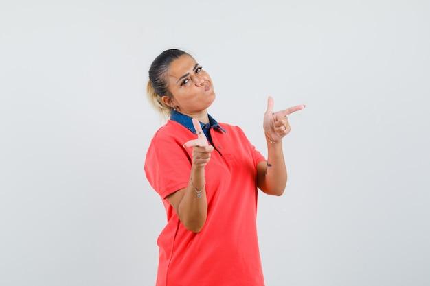 Jeune femme en chemise rouge pointant vers différentes directions avec l'index et à la jolie vue de face.