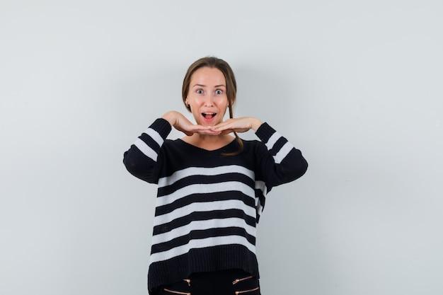 Jeune femme en chemise se tenant la main sous le menton et à la surprise
