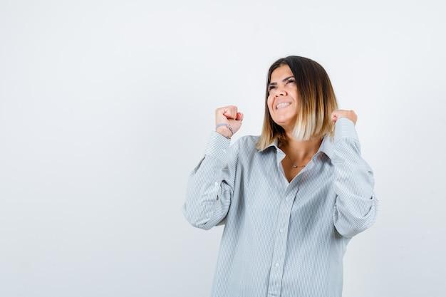 Jeune femme en chemise surdimensionnée montrant le geste du gagnant et semblant chanceuse, vue de face.