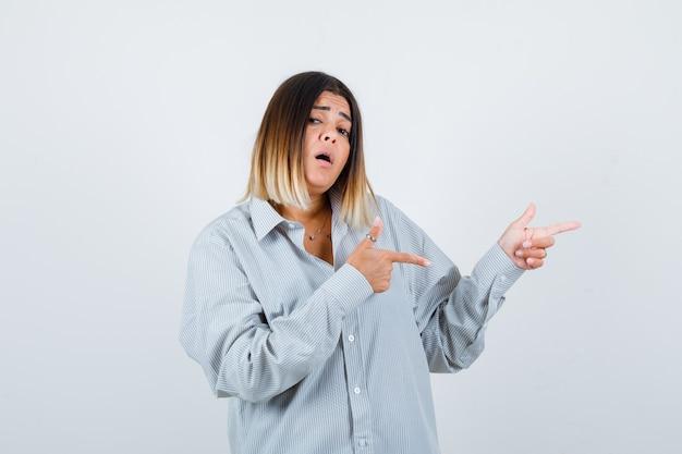 Jeune femme en chemise surdimensionnée pointant vers le côté droit et ayant l'air perplexe, vue de face.