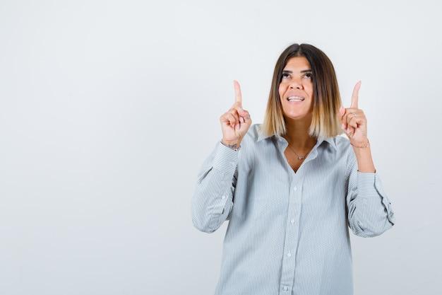 Jeune femme en chemise surdimensionnée pointant vers le haut et l'air heureux, vue de face.