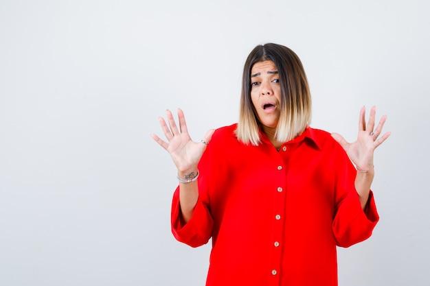 Jeune femme en chemise surdimensionnée rouge gardant les mains dans un geste de reddition et l'air anxieux, vue de face.