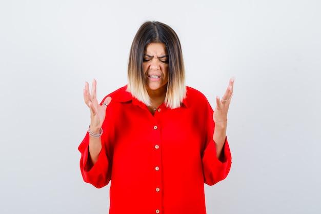 Jeune femme en chemise surdimensionnée rouge gardant les mains de manière agressive et semblant ennuyée, vue de face.