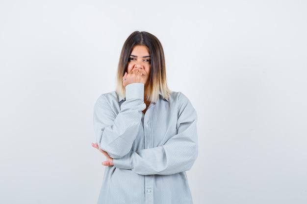 Jeune femme en chemise surdimensionnée se rongeant les ongles et semblant réfléchie, vue de face.