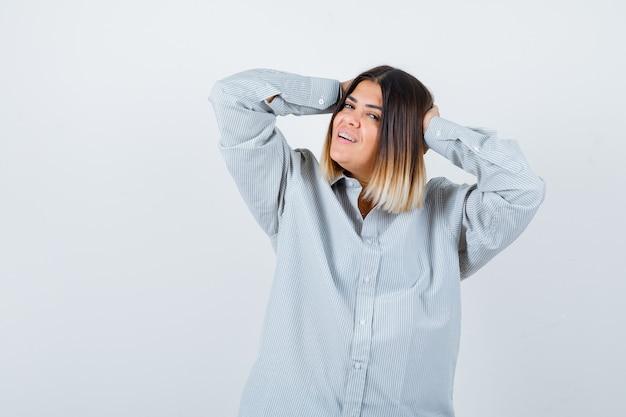 Jeune femme en chemise surdimensionnée tenant les mains sur la tête et l'air heureux, vue de face.