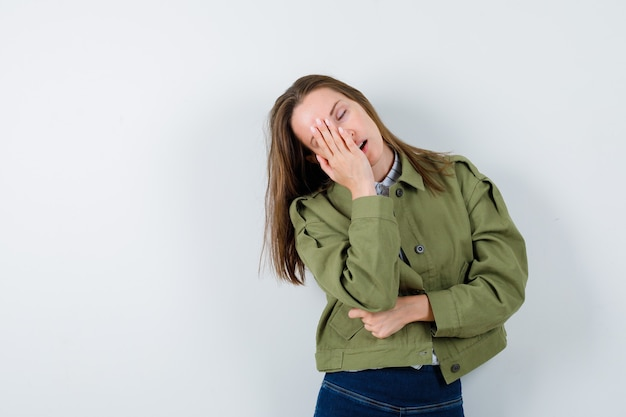 Jeune femme en chemise tenant la main sur le visage tout en posant et en ayant l'air endormi, vue de face.