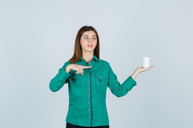 Jeune femme en chemise tenant une tasse de café en plastique tout en pointant vers le côté droit et à la recherche focalisée, vue de face.