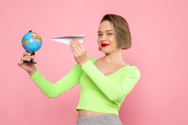 Jeune femme en chemise verte et jupe grise tenant avion en papier et petit globe