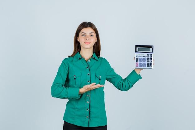 Jeune femme en chemise verte montrant la calculatrice et l'air confiant, vue de face.
